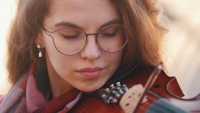 Mujer bonita joven que toca el viol?n a solas en p?blico almacen de video