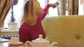 Mujer bonita joven que toma el selfie con el teléfono móvil en café metrajes