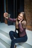 Mujer bonita joven que toma el selfie con el teléfono móvil mientras que se sienta en las escaleras en calle de la ciudad Fotos de archivo