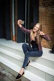 Mujer bonita joven que toma el selfie con el teléfono móvil mientras que se sienta en las escaleras en calle de la ciudad Fotografía de archivo