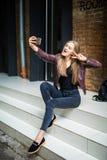 Mujer bonita joven que toma el selfie con el teléfono móvil mientras que se sienta en las escaleras en calle de la ciudad Imágenes de archivo libres de regalías
