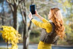 Mujer bonita joven que toma el selfie en el parque Imágenes de archivo libres de regalías