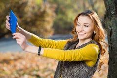 Mujer bonita joven que toma el selfie en el parque Foto de archivo libre de regalías