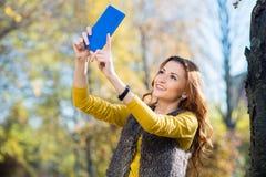 Mujer bonita joven que toma el selfie en el parque Foto de archivo