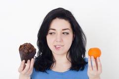 Mujer bonita joven que toma la decisión difícil entre la fruta y el mollete del chocolate Fotografía de archivo libre de regalías