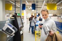 Mujer bonita, joven que usa el pago y envío del servicio del uno mismo en una tienda imagen de archivo