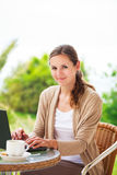 Mujer bonita, joven que usa un ordenador portátil en casa Imágenes de archivo libres de regalías