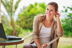 Mujer bonita, joven que usa un ordenador portátil en casa Imagen de archivo libre de regalías