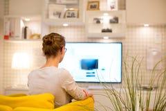 Mujer bonita, joven que ve la TV en casa Imagenes de archivo