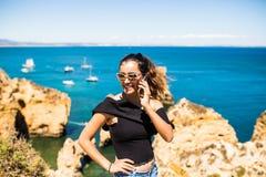 Mujer bonita latina que usa el teléfono elegante que adquiere el top de la roca del océano viaje y concepto activo de la forma de Fotografía de archivo libre de regalías