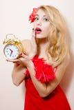Mujer bonita modela rubia joven divertida hermosa agitated con el despertador en el vestido rojo wonderingly que mira la cámara Imagenes de archivo