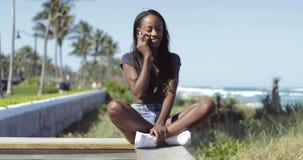 Mujer bonita negra que habla en el teléfono en la cerca almacen de video