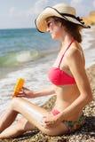Mujer bonita que aplica la loción de la protección solar en sus piernas Fotografía de archivo