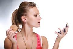 Mujer bonita que aplica maquillaje fotos de archivo