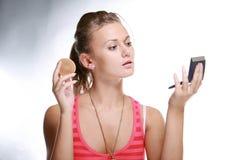 Mujer bonita que aplica maquillaje con el polvo fotografía de archivo