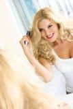 Mujer bonita que aplica su pelo con brocha Imágenes de archivo libres de regalías