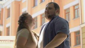 Mujer bonita que besa al novio gordo en la mejilla, fecha romántica al aire libre metrajes