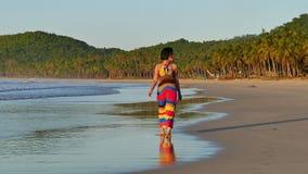 Mujer bonita que camina en la playa en la puesta del sol metrajes