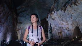 Mujer bonita que camina a través de una cueva