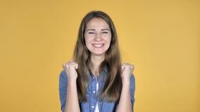 Mujer bonita que celebra el éxito aislado en fondo amarillo almacen de metraje de vídeo