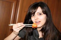 Mujer bonita que come el sushi Foto de archivo libre de regalías