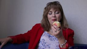 Mujer bonita que come la manzana dentro, concepto sano de la comida Mujer en rojo Primer en un fondo neutral almacen de video