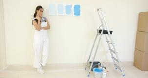 Mujer bonita que comtempla una opción de la pintura azul Foto de archivo libre de regalías