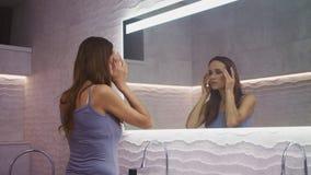 Mujer bonita que da masajes a la cara en cuarto de baño Mujer hermosa que hace yoga facial almacen de metraje de vídeo