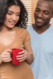 Mujer bonita que detiene la taza y al hombre que la miran fotografía de archivo libre de regalías