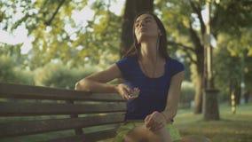 Mujer bonita que disfruta de música en banco de parque almacen de metraje de vídeo