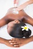 Mujer bonita que disfruta de un masaje de la exfoliación Fotografía de archivo