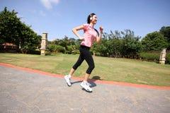 Mujer bonita que ejecuta al aire libre el entrenamiento en el parque Foto de archivo libre de regalías