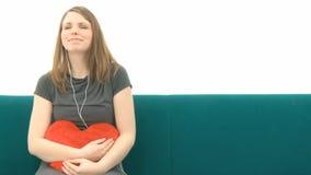 Mujer bonita que escucha la música y que abraza con una almohada del corazón almacen de metraje de vídeo