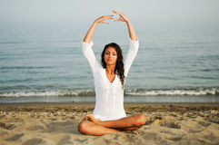 Mujer bonita que hace yoga en la playa Imagenes de archivo