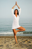 Mujer bonita que hace yoga en la playa Fotos de archivo