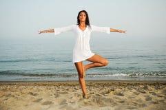 Mujer bonita que hace yoga en la playa Imagen de archivo libre de regalías
