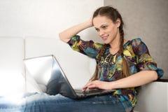 Mujer bonita que hojea en el ordenador portátil Imagenes de archivo