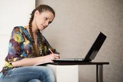 Mujer bonita que hojea en el ordenador portátil Fotos de archivo libres de regalías