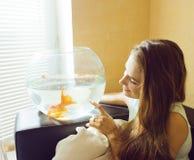 Mujer bonita que juega con el pez de colores en casa Fotografía de archivo libre de regalías