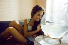 Mujer bonita que juega con el pez de colores en casa Fotos de archivo