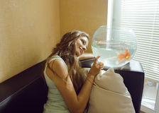 Mujer bonita que juega con el pez de colores en casa, Fotos de archivo
