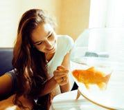 Mujer bonita que juega con el pez de colores en casa, forma de vida feliz de la mañana de la luz del sol, concepto moderno de la  Fotos de archivo libres de regalías