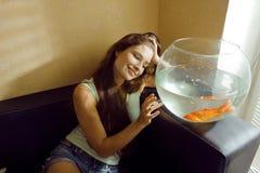 Mujer bonita que juega con el pez de colores en casa, mañana de la luz del sol Fotografía de archivo