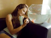 Mujer bonita que juega con el pez de colores en casa, mañana de la luz del sol Imagenes de archivo