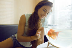 Mujer bonita que juega con el pez de colores en casa, mañana de la luz del sol Foto de archivo