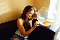 Mujer bonita que juega con el pez de colores en casa, mañana de la luz del sol Imagen de archivo