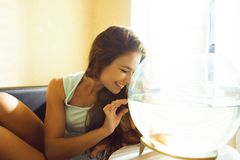 Mujer bonita que juega con el pez de colores en casa, mañana de la luz del sol Fotos de archivo libres de regalías