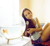 Mujer bonita que juega con el pez de colores en casa, SMI de la mañana de la luz del sol Imagen de archivo libre de regalías