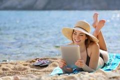 Mujer bonita que lee a un lector de la tableta en la playa el vacaciones Imagenes de archivo