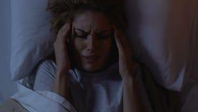 Mujer bonita que miente en cama en la noche, sufriendo de dolor de cabeza, síntomas de la jaqueca metrajes